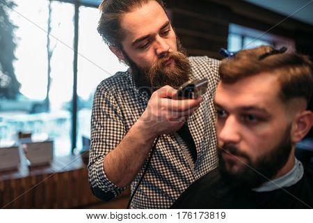 Barber working by clipper with hairstyle of client