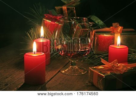 Glass of brandy or cognac, gift box and candle on the wooden table. Celebration composition