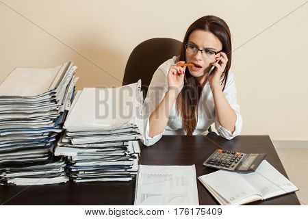 Female accountant using cell phone at workplace