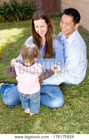 Portrait of a happy family and their biracial daughter.