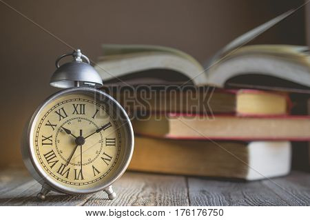 Roman Numeral in Vintage Alarm Clock and Open Book Background with Copy Space for Advertise about the Education or Nostalgia Concept