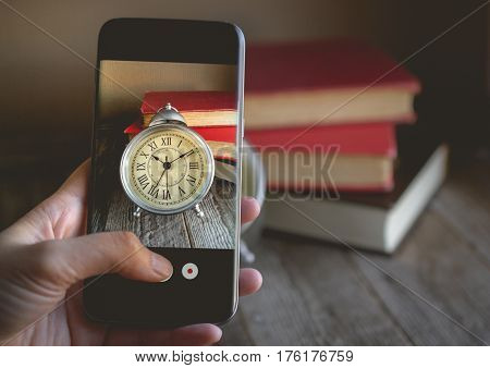 Taking a photo by Finger Pressing on Cellphone for Photograph Roman Numeral in Vintage Alarm Clock and Stack of Book with Copy Space. Image for Advertise about the Educate or Social Media Concept