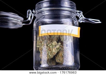 Detail of cannabis buds (maui skunk strain) on a glass jar isolated over black background - medical marijuana concept