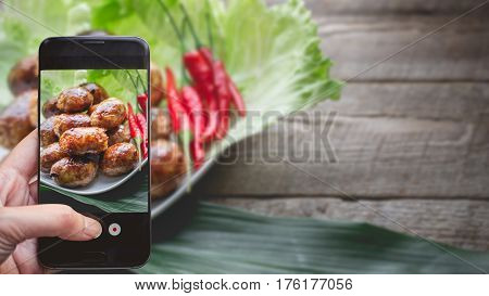 Taking a photo by Finger Pressing on Smartphone for Photograph Thai Delicious Sausage on the White Plate and Wooden Background with Copy Space in Rustic Vintage Style. Image for Food Concept Advertise or Website Promote.
