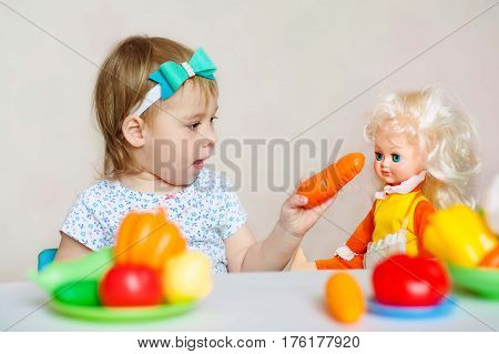 Little cute girl playing with her doll. Child feeding doll in white nursery. Toddler kid in a playroom. Kids feed dolls and cook in toy kitchen.