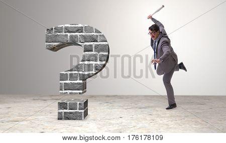 Angry man with baseball bat hitting question mark