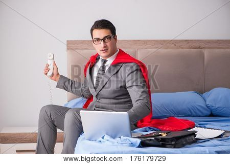 Super hero businesswoman working in bed