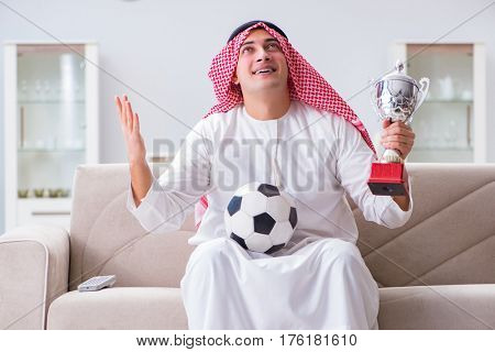 Arab man watching sport football at tv
