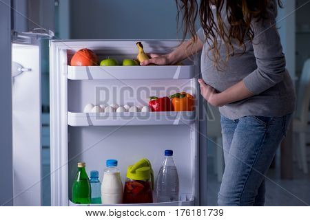 Pregnant woman near fridge looking for food and snacks at night
