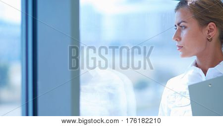 Businesswoman standing against office window holding documents in hand