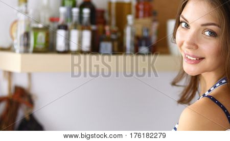 Young woman standing in kitchen at home