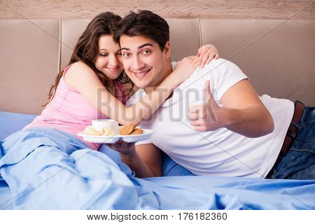 Happy family having breakfast in bed