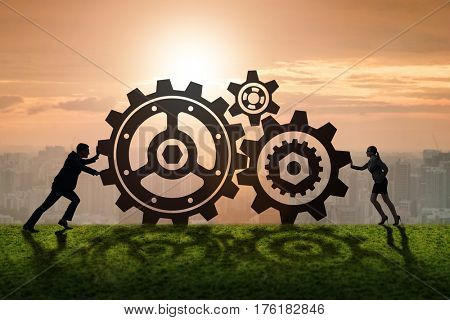 Businesspeople in teamwork example with cogwheels
