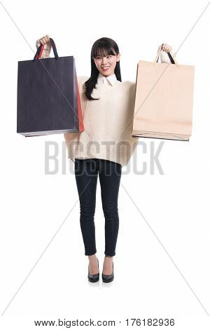 Studio portrait of twenties Asian woman happily shopping