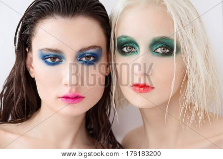 Glamour portrait of beautiful women. Woman with wet hair. Color make up green eye shadow red lipstick. trend make up.Two beautiful young girls in creative make-up. Blonde and brunette.