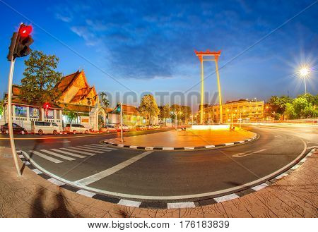 The giant swing with temple of buddha at twilight time with fish-eye lens at bangkok city Thailand