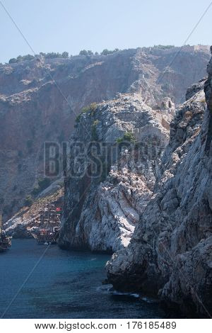 View from sea of Alanya castle rock with castle walls and remains of ancient monestary located on cape Jilvarda