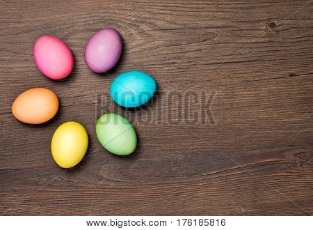 Colorful Easter Eggs arranged on a wooden background.