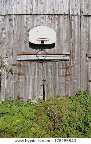 An old weathered barn is the home of a basketball backboard and hoop