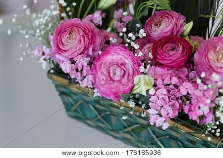 Closeup of flower arrangement in basket with pink ranunculus and austeria with central ranunculus in focus and other flowers blurred