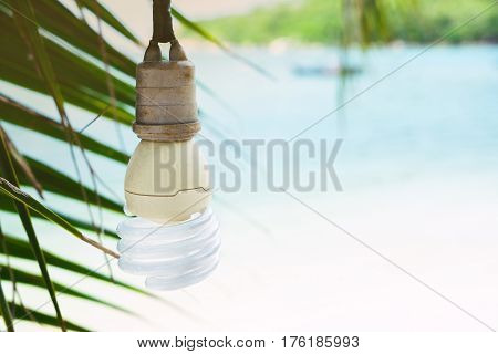 Electric energy-saving fluorescent lamp on a tropical landscape background. The concept of energy saving and ecology.