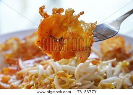 crispy fried egg stab in fork on plate
