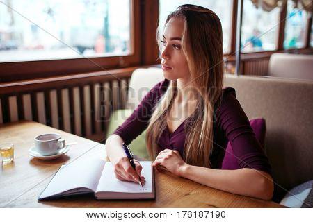 Female writing in notebook in restaurant.