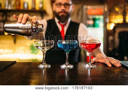 Bartender making alcohol beverages in nightclub