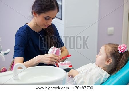 Pediatric dentist educating a smiling little girl about proper tooth-brushing, demonstrating on a model. Early prevention, raising awareness, oral hygiene demonstration concept