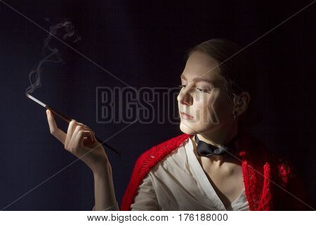 Charming lady with mouthpiece in a red shawl on a black background