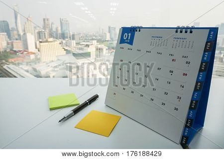 January calendar with mock up posit and pen for making note