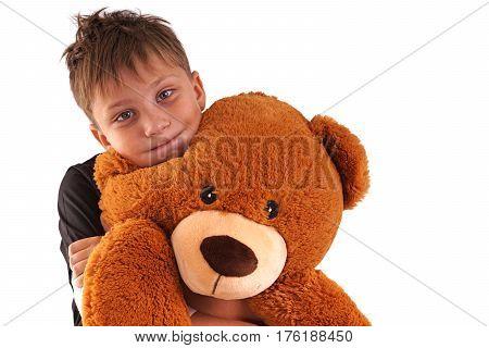 Boy embraces plush bear and smile, isolated on white background