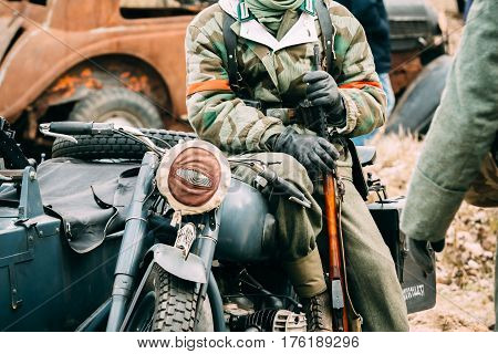 German soldier Wehrmacht sits on a motorcycle with an automatic rifle in his hands