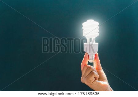 electricity, environment and ecology concept - close up of hand holding energy saving light bulb or lamp
