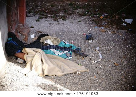 The sleeping berth of a homeless under a bridge with covers rubbish and food rests.