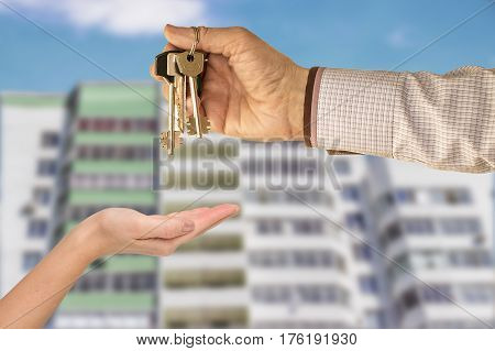 Businessman handing a key to success over a woman palm. a house in the background.