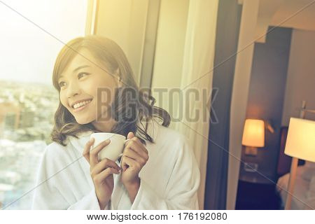 Asian woman holding a cup of coffee in the morning.
