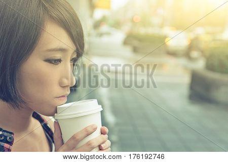 Asian girl holding cup of coffee at street in raining day in Taipei, Taiwan.