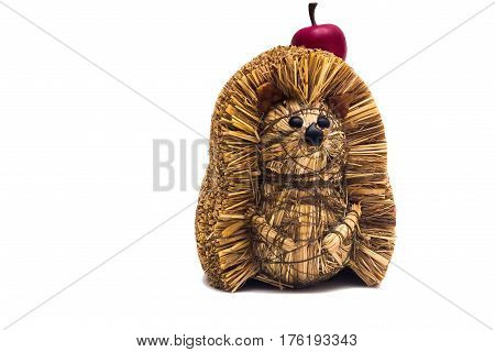 Handmade hedgehog made of hay with artificial apple isolated on white background