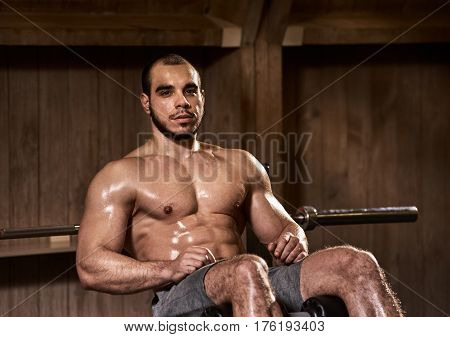 Young healthy muscular man exercising abdominals in fitness club