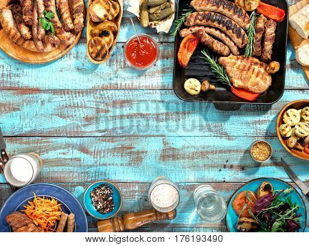 Different food cooked on the grill on the blue wooden table on a sunny day grilled steak grilled sausage grilled vegetables and lager beer. Outdoors Food Concept