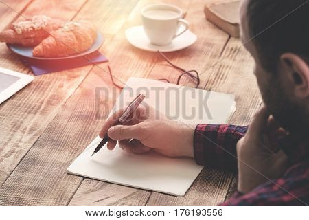 Male hands writing on notebook sitting at a wooden table at coffee shop
