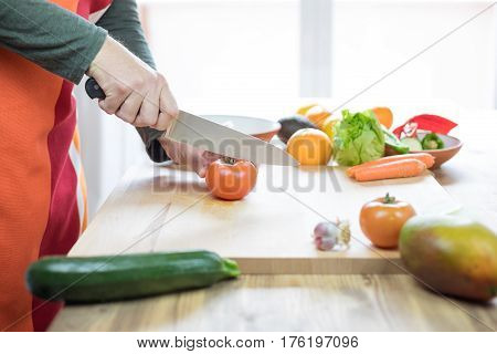 Hands Of Man Cutting Tomato On Wooden Cutting Board