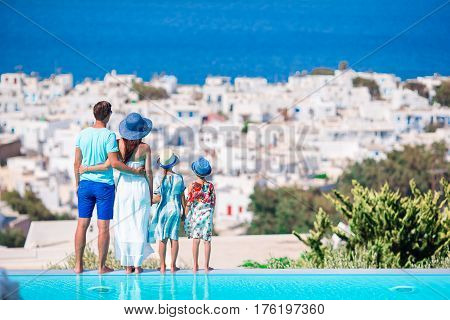 Family of four on european vacation on the edge of pool