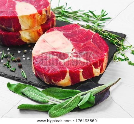 meat beef veal shank slices meat for Osso Buco cooking on white wooden background. Ingredients for beef meat Osso Buco sage leaves thyme rosemary pepper salt pepperl.