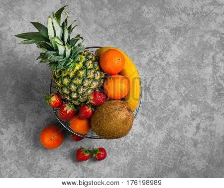 Exotic tropical fruit pineapple coconut berries strawberries mandarins clementines bananas in metal bowl basket of fruit on gray background. Top view from above and copy space.