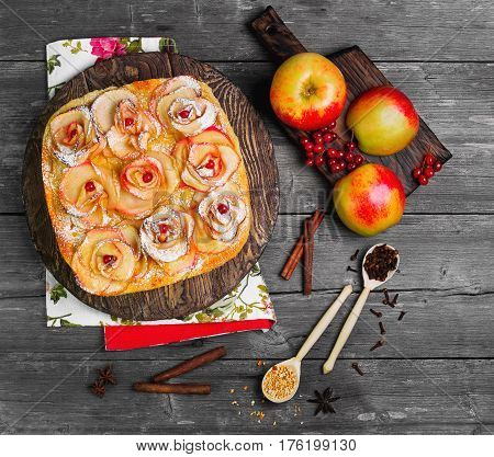 Fruit apple pie tartlet (cake). On top of the pie cake in shape of apples rose flowers. Fresh fruit apples for pie cake. Spice cloves star anise berries orange peel. Gray wood background. Top view.