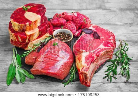 Different types of meat beef on round board. Herbs for an assortment of beef meat basil thyme rosemary sage leaves pepper. Light white wooden background. Top view from above and copy space.