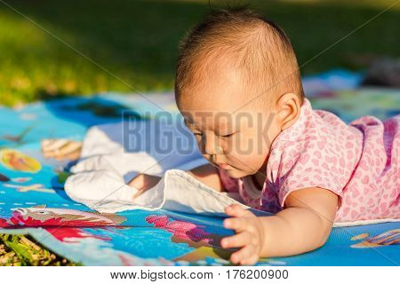 Cute Asian Baby Laying Down On Ground At Park
