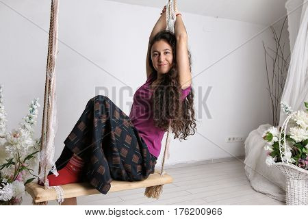 Young girl in long skirt sitting on swing in white room.